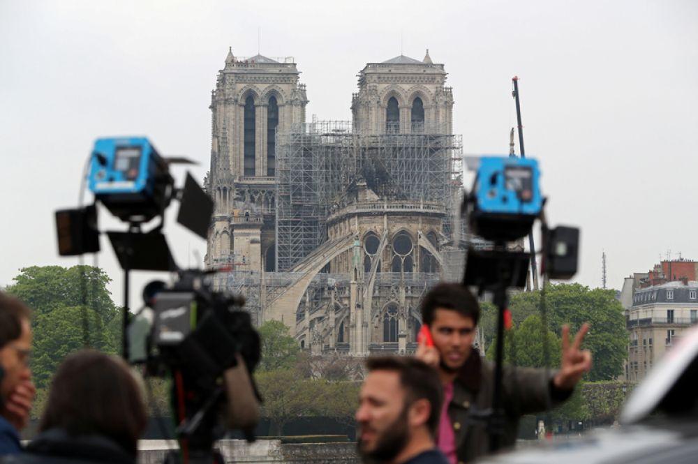 Журналисты на фоне сгоревшего собора.