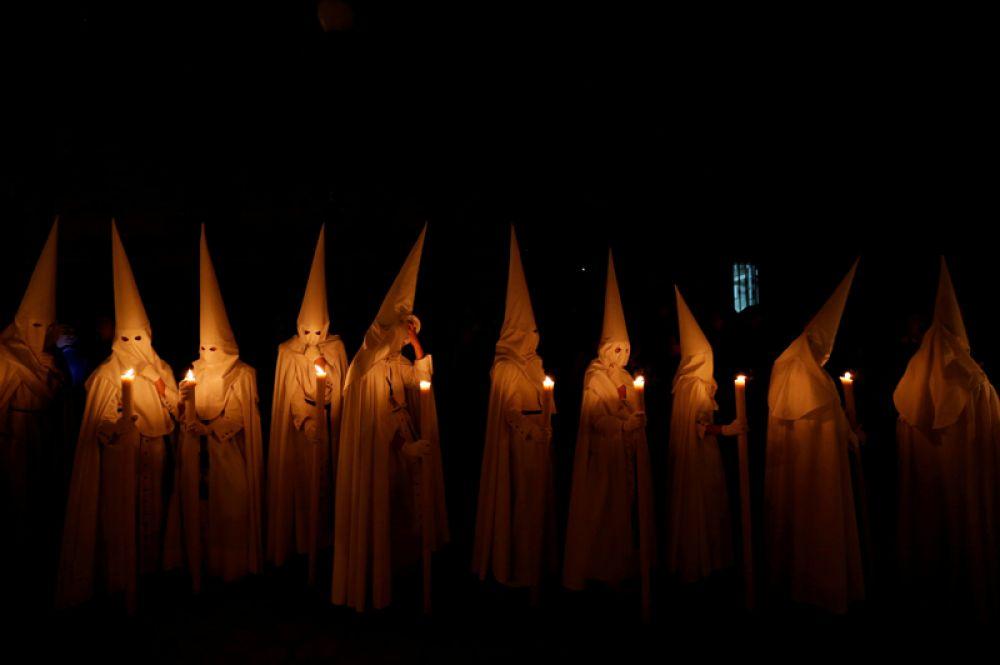 Члены братства La Paz принимают участие в шествии во время Страстной недели в Севилье, Испания.