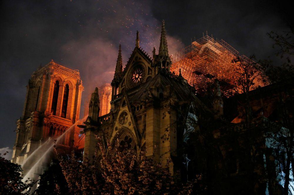 Пожарные тушат собор Парижской Богоматери, загоревшийся вечером 15 апреля, Франция.