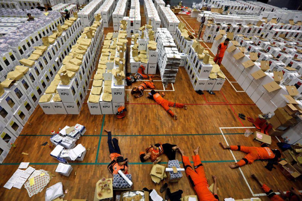 Рабочие во время перерыва между подготовкой предвыборных печатных материалов на складе в Джакарте, Индонезия.