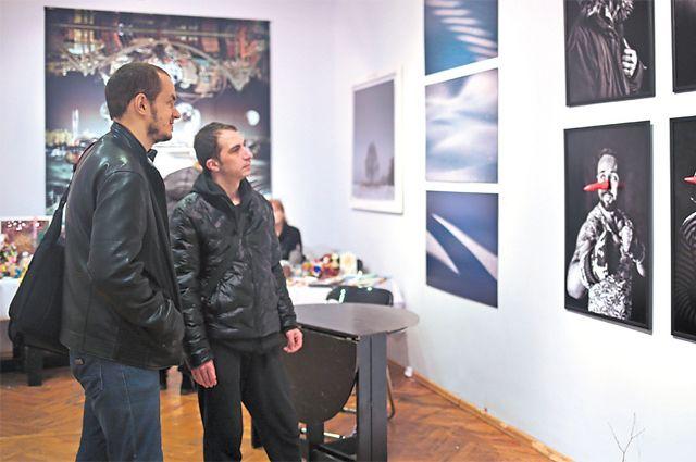 Посетители галереи «Нагорная» знакомятся с выставкой фоторабот.