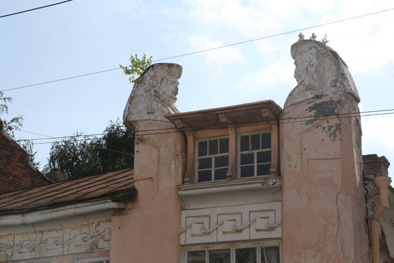 На пилонах здания установлены бюсты-авгуры в виде человеческих голов, склонившихся над шахматной доской.