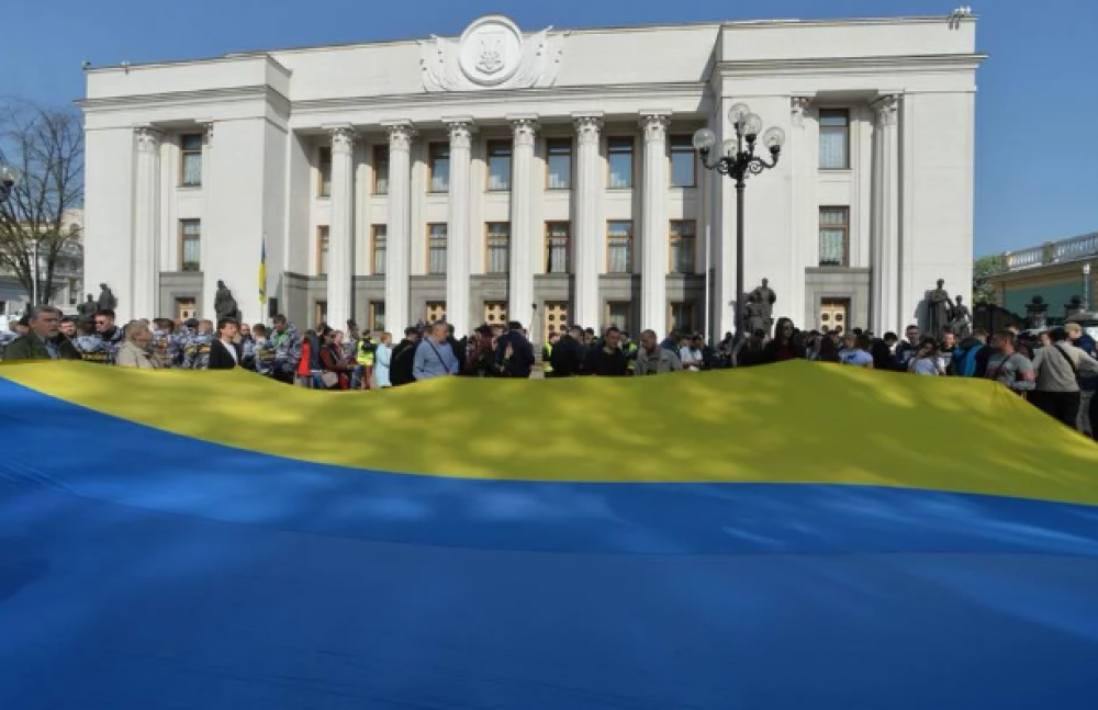 Под Радой в этот день собрались люди в поддержку законопроекта и развернули огромный флаг Украины.