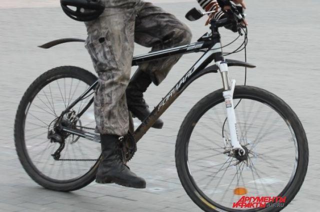 Мужчина на велосипеде двигался по проезжей части в потоке машин.
