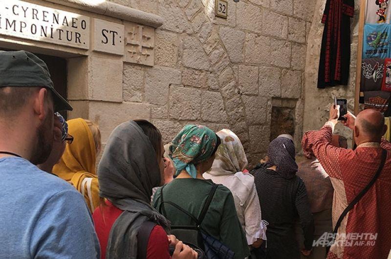 Паломники, прикладывающиеся к отпечатку руки Иисуса на Виа Долороса.