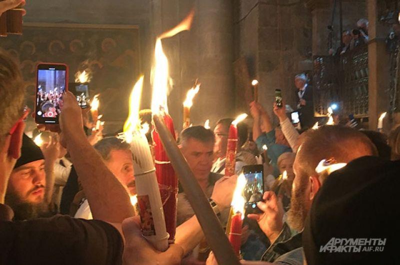 Верующие передают огонь друг другу.