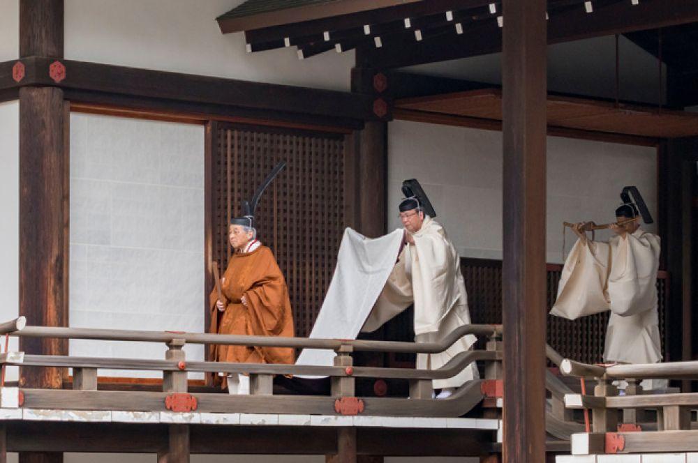 Император Японии Акихито идет на ритуал.