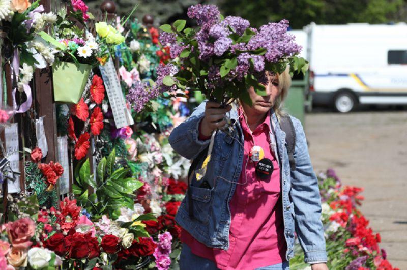 Женщина несет цветы к Дому профсоюзов.