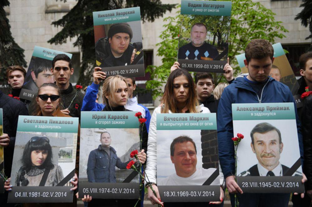 Участники акции «Помним» движения «Антимайдан» уздания посольства Украины держат портреты людей, погибших при пожаре 2мая 2014в Доме профсоюзов вОдессе.