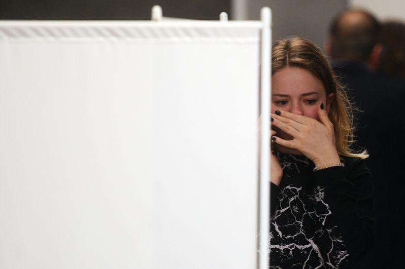 Девушка возле комнаты психологической помощи, организованной для пассажиров и их родственников.