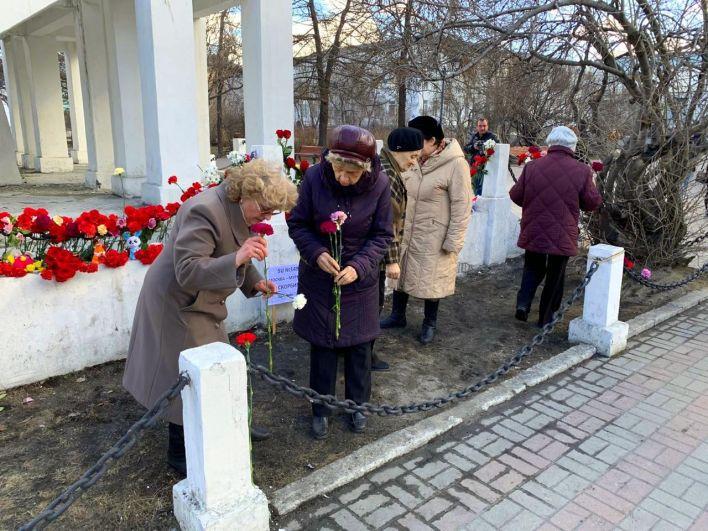 Жители Мурманска несут цветы к Памятнику жертвам интервенции.