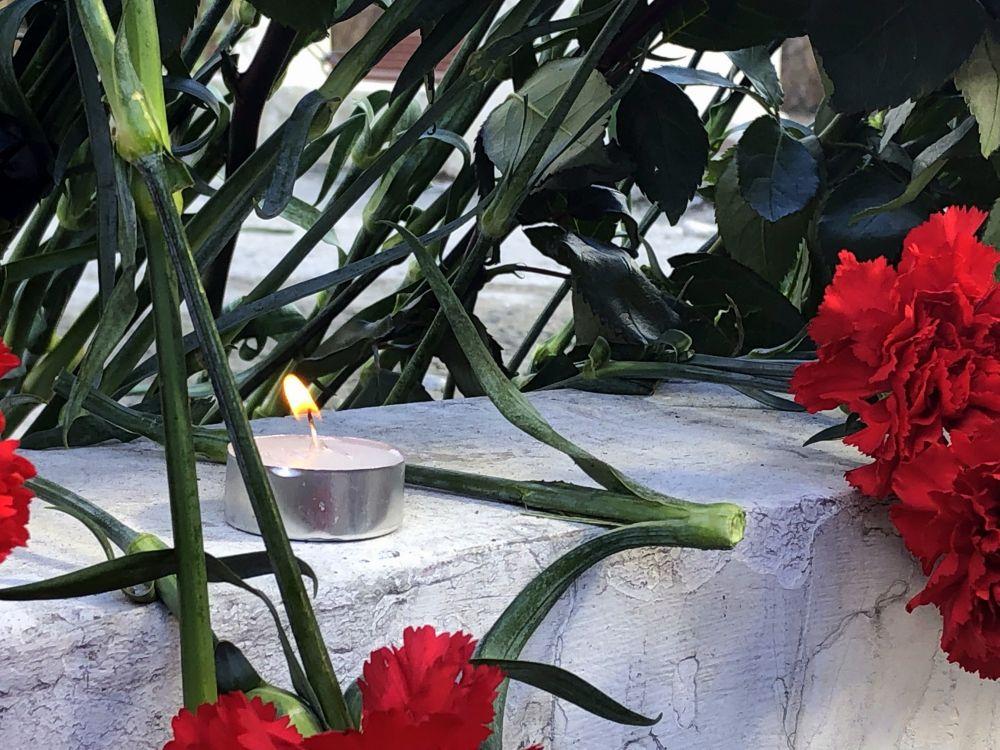 Люди зажигают свечи в память о погибших.