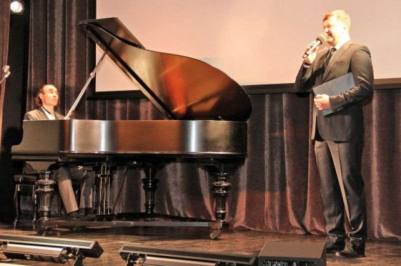 Ведущий мероприятия, артист «Петербург-концерта» Антон Денисов читает стихотворение под аккомпанемент пианиста Олега Вайнштейна.