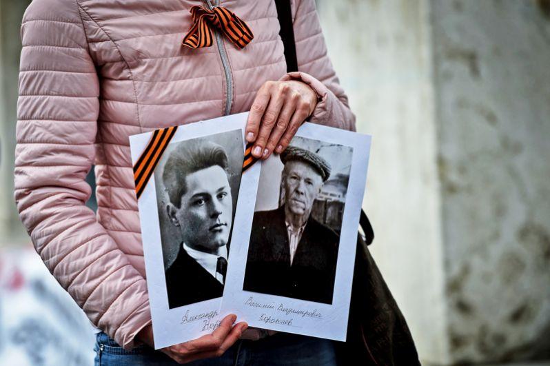 Фотографии в руках у участницы акции «Бессмертный полк» в Риме.