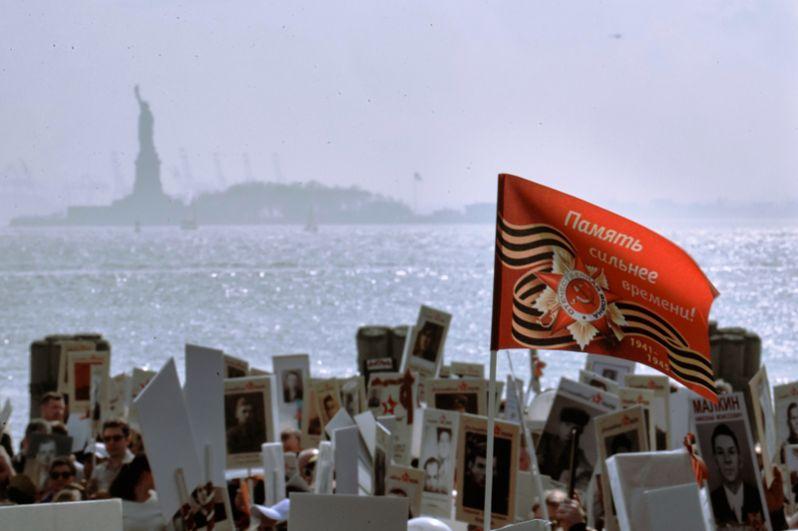 Транспаранты и флаг в руках участников акции «Бессмертный полк» в Нью-Йорке.