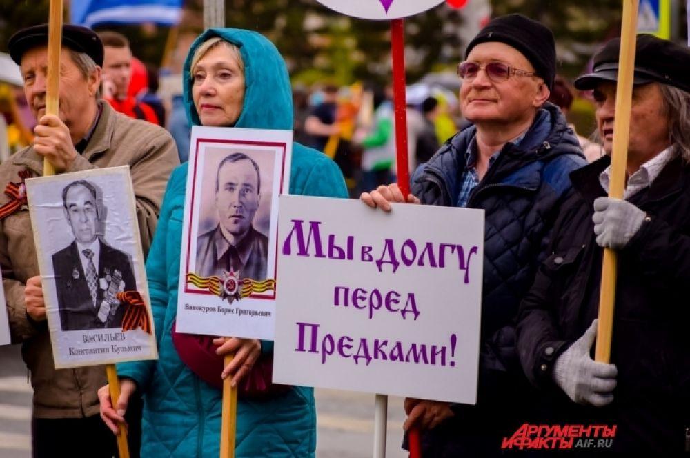 Люди несли в руках таблички с фотографиями своих родных, воевавших на фронте.
