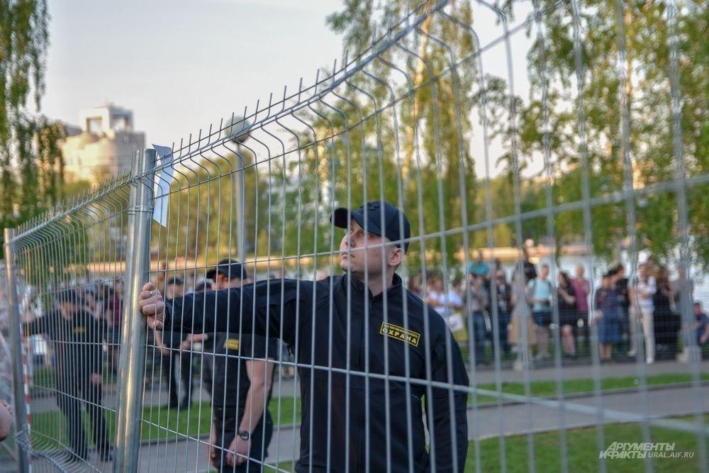 Сотрудник ЧОП читает листовку, повешенную на забор.