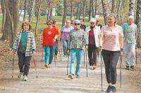 Преподаватель поскандинавской ходьбе Елена Адамян ведёт своих учеников поаллеям парка.