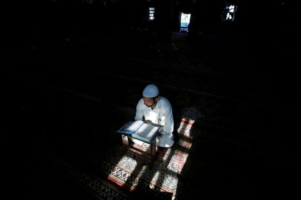 Мусульманин читает Коран в храме во время священного месяца Рамадан в Сринагаре, Индия.