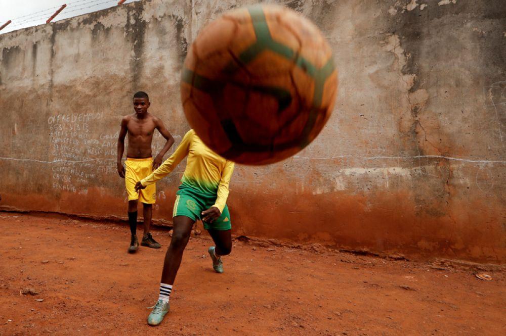 Молодая девушка играет в футбол с друзьями возле своего дома в Яунде. Камерунские женщины получили возможность обучаться у профессиональных тренеров в Rails Foot Academy.