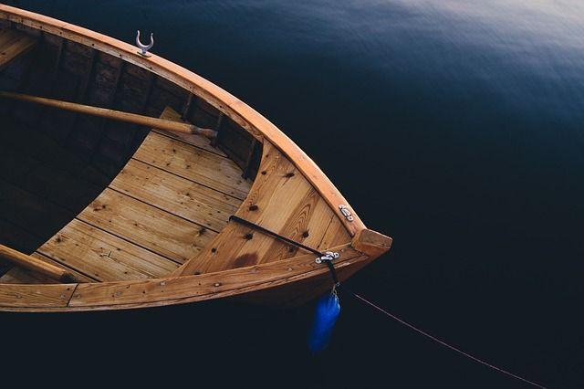 Дедушка вместе с внуком вышли на деревянной гребной лодке на воду.