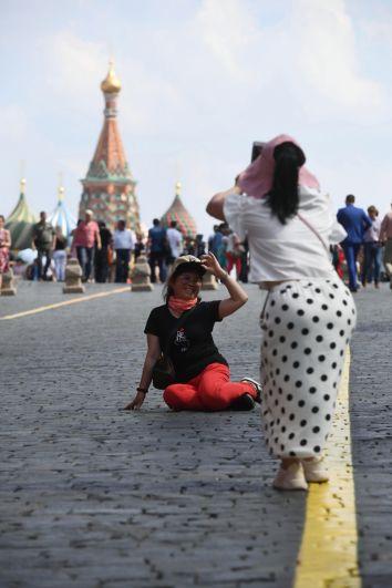 Туристы фотографируются на Красной площади.