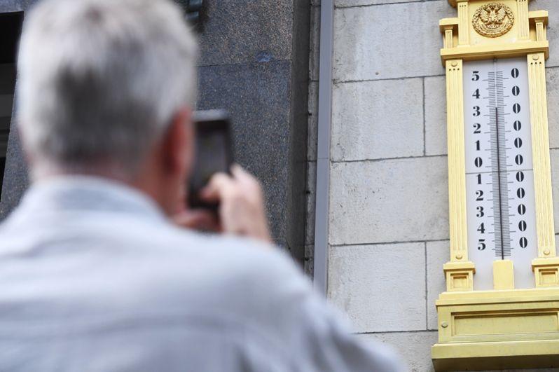Мужчина фотографирует термометр на здании Государственной Думы.