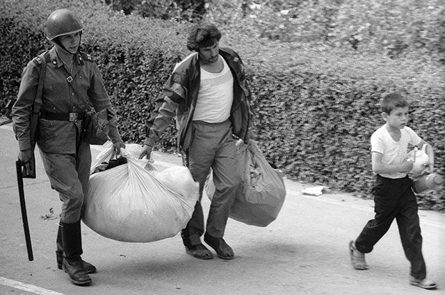 Солдат внутренних войск помогает беженцам, Фергана, Узбекистан, июнь 1989 г.