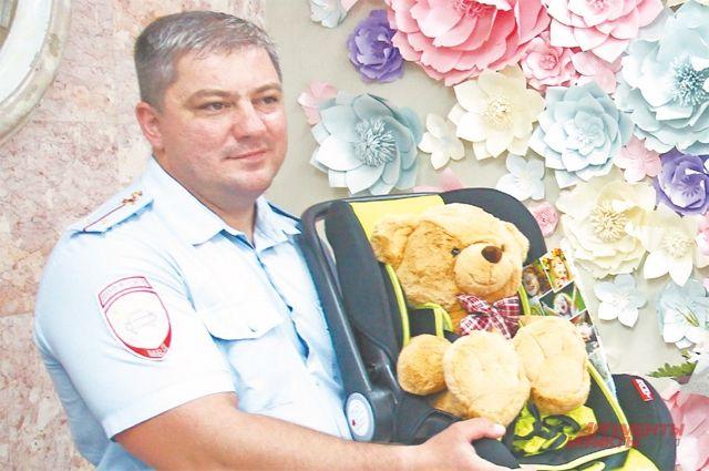 Капитан Серёгин с подарком для молодых родителей.