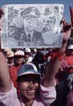 Демонстрант держит в руках карикатуру на премьер-министра Ли Пэна.