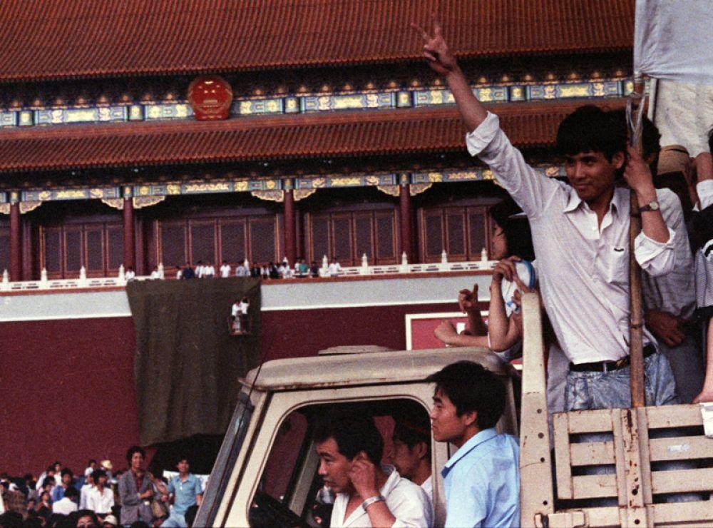 Один из демонстрантов поднимает руку в знак победы после того, как им удалось задрапировать портрет Мао Цзэдуна.