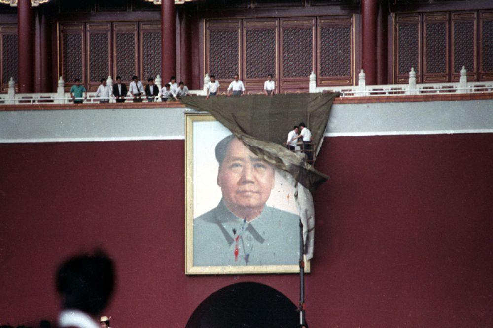 Мужчины пытаются задрапировать портрет Мао Цзэдуна на Воротах Небесного спокойствия на площади Тяньаньмэнь.