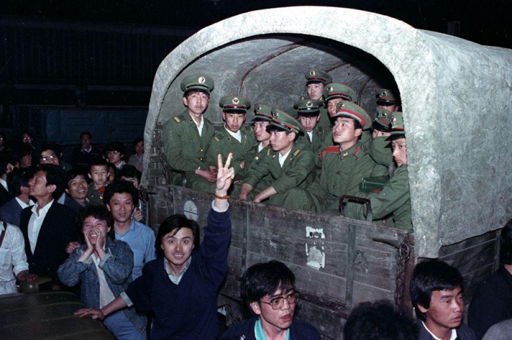 Протестующие окружают военных в пригороде Пекина, чтобы не дать им продвинуться к площади Тяньаньмэнь.