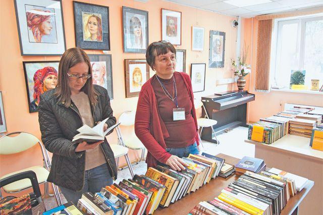 Читательница Светлана Игорева выбирает книги с заведующей сектором Еленой Николаевной.