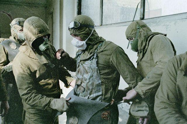 Люди, занимающиеся расчисткой кровли повреждённого реактора, одевают защитные костюмы.