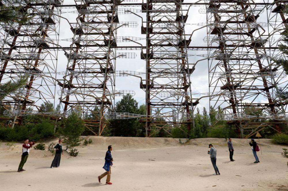 Туристы фотографируются у загоризонтной радиолокационной станции «Дуга», остановленной в связи с аварией.