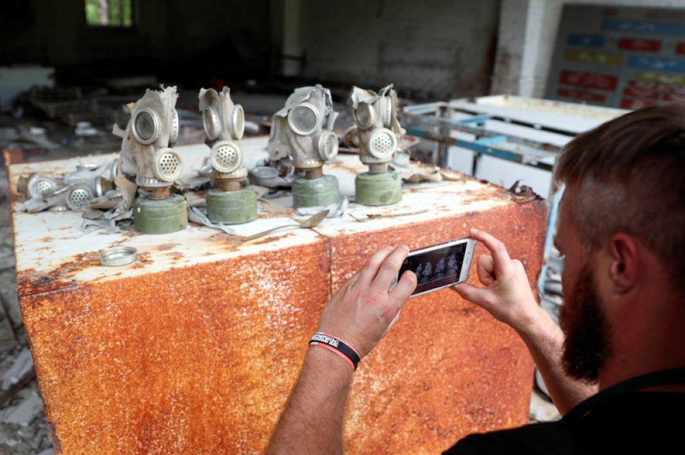 Посетитель фотографирует противогазы на заброшенной базе рядом с ЧАЭС.