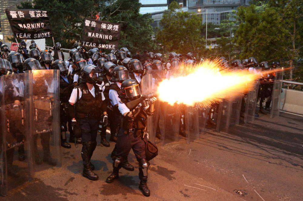 Полицейские применяют слезоточивый газ во время массовой демонстрации против законопроекта об экстрадиции в Китай, Гонконг.