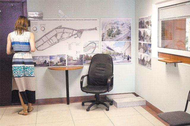 Жительница Дорогомилова рассматривает в управе экспозицию, посвящённую реализации программы «Мой район».
