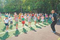 Физрук Иван Артёмов проводит 10-минутную зарядку для детей во дворе школы.