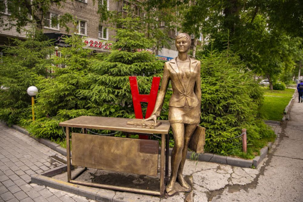 А эту важную даму точно не встретишь на рынке (смотри первое фото). Памятник деловой женщине расположен около дома №3 по улице Мичурина. Он сделан по заказу одной из компаний, расположенный в здании по этому адресу: не сложно догадаться, что руководит этой организацией женщина. Бизнес-леди одета в деловой костюм, держит в руках портфель и опирается на рабочий стол. В народе скульптуру называют памятником секретарю, карьеристке и даже учительнице: стол действительно напоминает школьную парту.