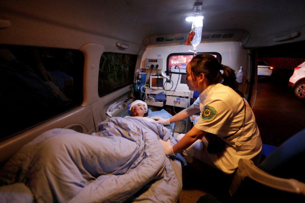Медицинский работник оказывает помощь пострадавшей женщине в машине скорой помощи.