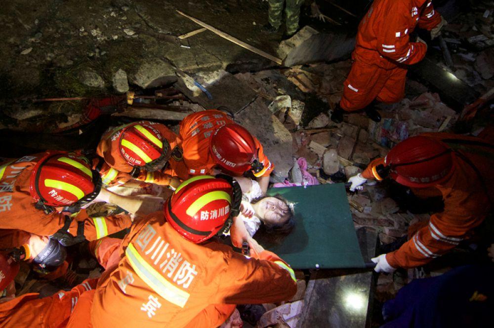Спасатели укладывают раненую женщину на носилки.