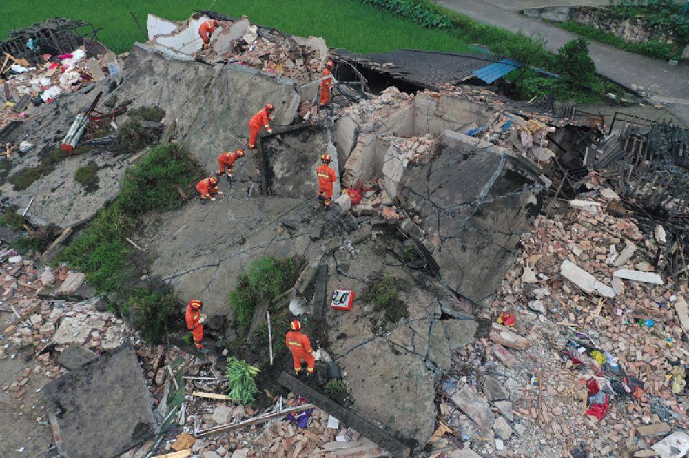 Спасатели на развалинах дома после землетрясения.