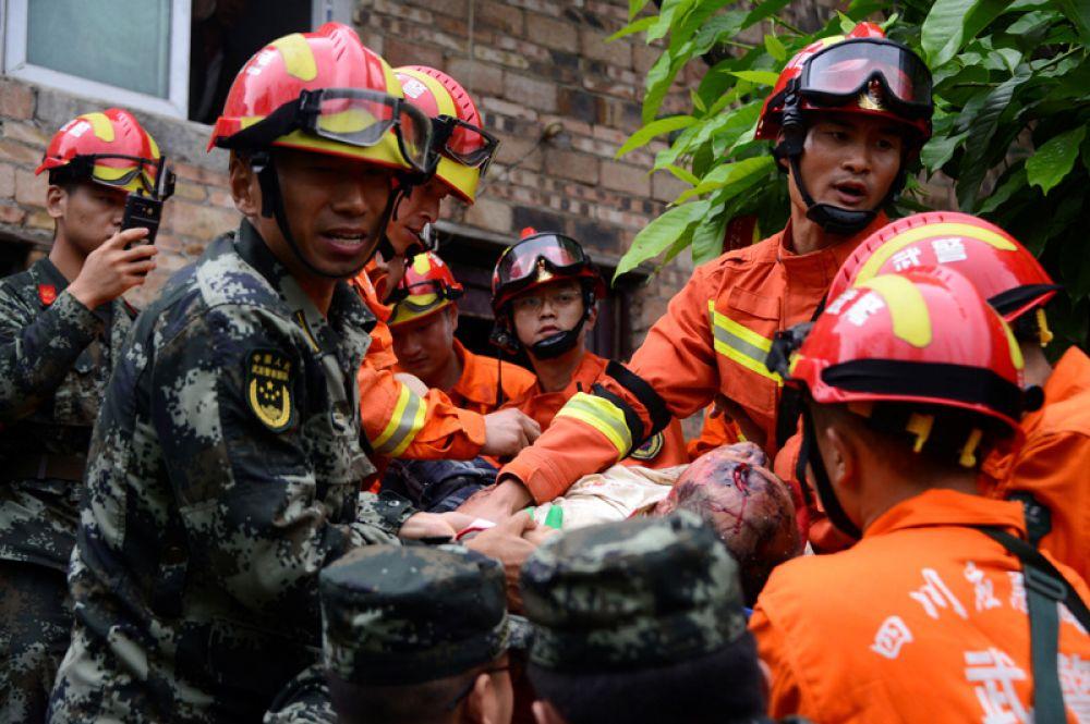Спасатели несут раненого на носилках.