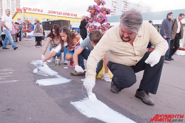 Активисты закрашивают рекламу спайсов.