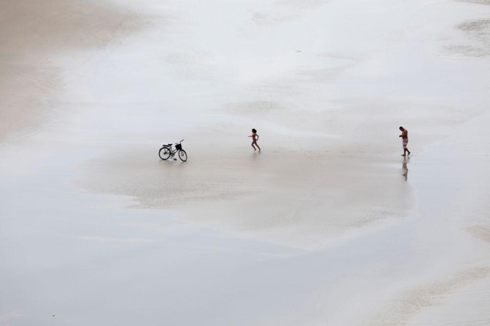 Девочка, сопровождаемая родственником, бежит к велосипеду на пляже в Гуаруже, Бразилия.
