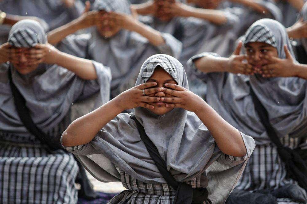 Мусульманские студенты посещают уроки йоги в школе перед Международным днем йоги в Ахмедабаде, Индия.