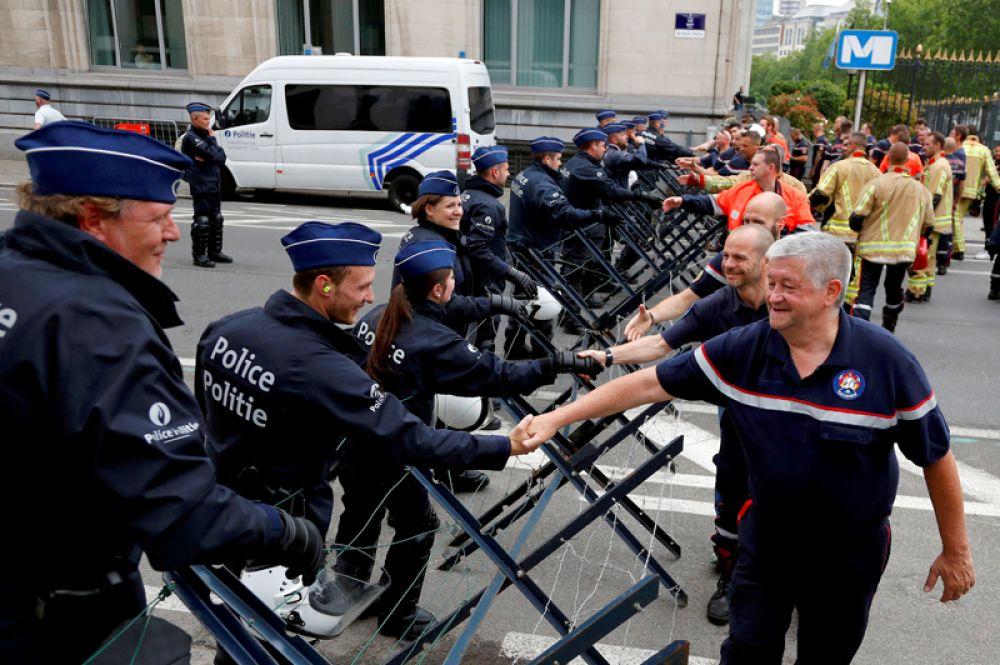 Бельгийские пожарные приветствуют полицейских во время протеста за улучшение условий труда в Брюсселе.