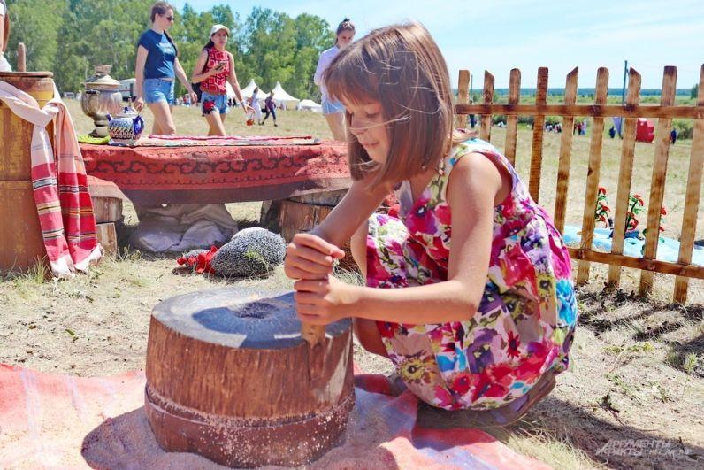 На Бажлвке можно прикоснуться ко множеству древних ремёсел и занятий: маленькая гостья пробует молоть зерно так, как это делали несколько веков назад.